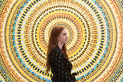 © Licensed to London News Pictures. 19/09/2019. London, UK. A visitor views a painting titled Cardinal (2019) by British artist Damien First. The work is part of a new exhibition titled Mandalas showing at the White Cube Gallery Mason's Yard. Photo credit: Ray Tang/LNP