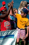 10 year old kids slapping high fives at Lake Calhoun.  Minneapolis  Minnesota USA