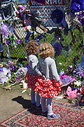 Young twin girls looking at all of the Prince memorial items surrounding Paisley Park Studios. Chanhassen Minnesota MN USA