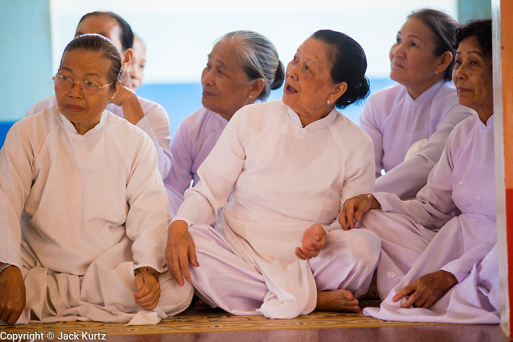 """29 MARCH 2012 - TAY NINH, VIETNAM:  Women in the Cao Dai wait for noon prayers to start at the Cao Dai Holy See in Tay Ninh, Vietnam. Cao Dai (also Caodaiism) is a syncretistic, monotheistic religion, officially established in the city of Tây Ninh, southern Vietnam in 1926. Cao means """"high"""" and """"Dai"""" means """"dais"""" (as in a platform or altar raised above the surrounding level to give prominence to the person on it). Estimates of Cao Dai adherents in Vietnam vary, but most sources give two to three million, but there may be up to six million. An additional 30,000 Vietnamese exiles, in the United States, Europe, and Australia are Cao Dai followers. During the Vietnam's wars from 1945-1975, members of Cao Dai were active in political and military struggles, both against French colonial forces and Prime Minister Ngo Dinh Diem of South Vietnam. Their opposition to the communist forces until 1975 was a factor in their repression after the fall of Saigon in 1975, when the incoming communist government proscribed the practice of Cao Dai. In 1997, the Cao Dai was granted legal recognition. Cao Dai's pantheon of saints includes such diverse figures as the Buddha, Confucius, Jesus Christ, Muhammad, Pericles, Julius Caesar, Joan of Arc, Victor Hugo, and the Chinese revolutionary leader Sun Yat-sen. These are honored at Cao Dai temples, along with ancestors.    PHOTO BY JACK KURTZ"""