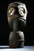 old fabric gas mask with broken plastic eyepieces and canister