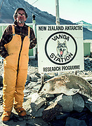 New Zealand mountaineer and Scott Base leader Norman Hardie with Vanda station sign, Dry valleys, Antarctica.