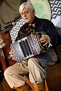 Argentinian man playing the acordian, on a traditional estancia, Lujan, Argentina.