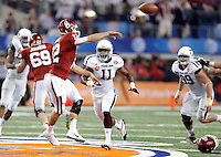 Oklahoma Sooners quaterback Landrty Jones (12) is pressured by Texas A&M Aggies linebacker Jonathan Stewart (11) during the 77th AT&T Cotton Bowl Classic between the Texas A&M University Aggies and the Oklahoma University Sooners at Cowboys Stadium in Arlington, Texas. Texas A&M wins the 77th AT&T Cotton Bowl Classic against Oklahoma, 41-13.