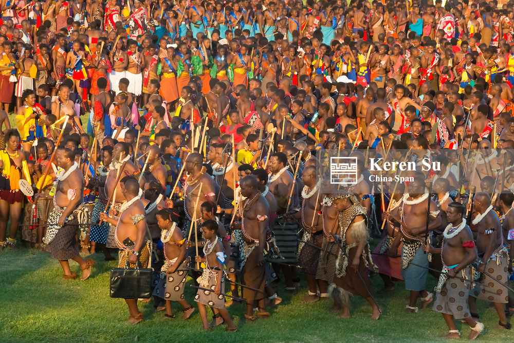 Swazi king (holding red scepter stick) and his warriors parade with girls at Umhlanga (Reed Dance Festival), Swaziland