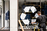 A male retaill contractor pastes a recyclig sticker on to the window surface at the Jermyn Street branch of Charles Tyrwhitt, on 27th April 2021, in London, England. Now that their branches are re-opening after pandemic lockdowns, mens clothing retailer Charles Tyrwhitt are offering a recycling service for old shirts.