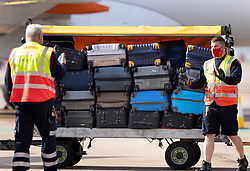 © Licensed to London News Pictures. 17/05/2021. Crawley, UK. ground crew prepare to load baggage on an EasyJet flight ahead of departure to Faro in Portugal from Gatwick Airport as step three on the roadmap out of lockdown begins. Travel to 12 countries on the green list is allowed from today. Holiday-makers returning home from green listed countries, including Portugal, Gibraltar and Iceland will not have to self-isolate on return. Various hospitality rules are also changing today - with pubs and restaurants allowed to serve seated customers indoors. Photo credit: Peter Macdiarmid/LNP