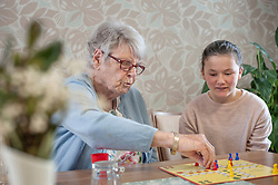 Girl playing ludo board game with senior women in rest home