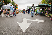 People walk through the Farmer's Market in Fayetteville on Saturday, May 17, 2014, in Fayetteville, Ark. Photo by Beth Hall