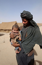 ZHARE DASHT,AFGHANISTAN - SEPT. 4: A Pashtun Afghan who was living in a camp for displaced people around Spin Boldak, near the border of Pakistan and southern Afghanistan, is relocated to the encamptment of Zhare Dasht by the UNHCR September 4, 2002.  As an estimated 1.6 million Afghan refugees return to Afghanistan,  ethnic Pashtuns from northern Afghanistan are seeking safety in   camps in the south. Numbering up to 120,000,  Pashtuns are fleeing the Tajik- and Uzbek-dominated cities of the north out of fear and prefer to live in the dismal camps like Zhare Dasht which is set in the middle of a desert surrounded by mines about 30 kilometers west of Kandahar. (Photo by Ami Vitale/Getty Images)