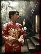 A man in traditional outfit holds encense sticks in a temple of Hue, Vietnam, Southeast Asia