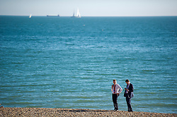 © London News Pictures. 23/09/2013 . Brighton, UK.  Two conference delegates enjoy the sunshine on Brighton beach while taking a break from the 2013 Labour Party Annual Conference which is being held at The Brighton Centre. Photo credit : Ben Cawthra/LNP