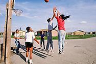 Pine Ridge Sioux Indian Reservation, Oglala, South Dakota, Oglala Sioux (Lakota) Indian boys play basketball, government housing complex