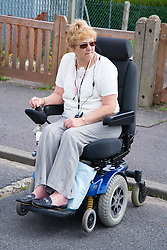 Female wheelchair user checking for oncoming traffic before crossing a road,