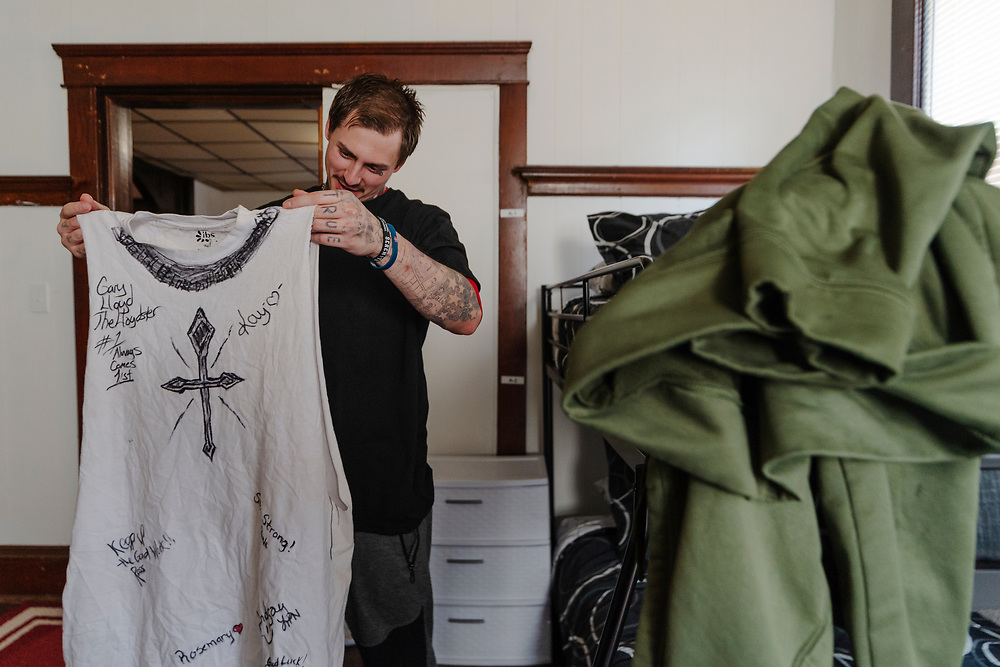 Steven Kelly holds up a shirt signed by his friends and others in rehab while unpacking at the Spartan House in Charleston, W.Va., on Friday, March 22, 2019.