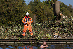 An HS2 security guard monitors an anti-HS2 activist swimming in the Grand Union Canal to halt tree felling works alongside HOAC lake in connection with the HS2 high-speed rail link on 21 September 2020 in Harefield, United Kingdom. Anti-HS2 activists continue to try to prevent or delay works for the controversial £106bn HS2 high-speed rail link on environmental and cost grounds from a series of protection camps based along the route of the line between London and Birmingham.