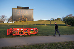 © Licensed to London News Pictures. 18/04/2021. London, UK. A man jogs past a sign warning of a 10pm closure at Primrose Hill in North London. A curfew has been put in to place at the park over the weekend to prevent large gatherings in the evening. Photo credit: Ben Cawthra/LNP