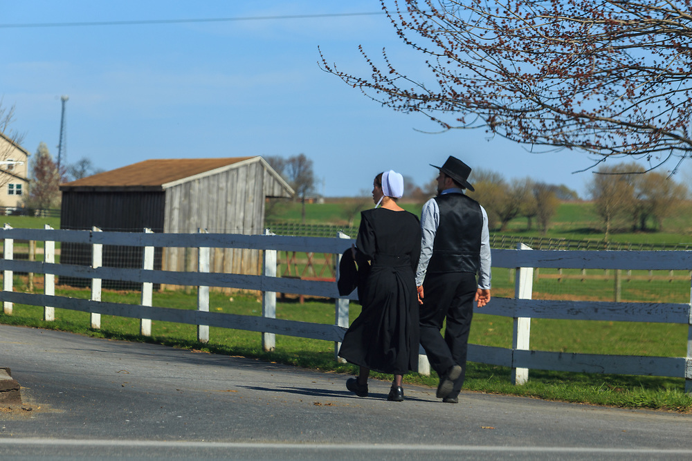 Ronks, PA, USA - April 22, 2018:  An Amish man and woman walk down a farm lane in rural Lancaster County.