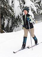 a woman cross country skis on a groomed ski trail on the Mount Tahoma Trails hut to hut ski trail system near Mount Rainier in the Cascade Range, Ashford, WA, USA