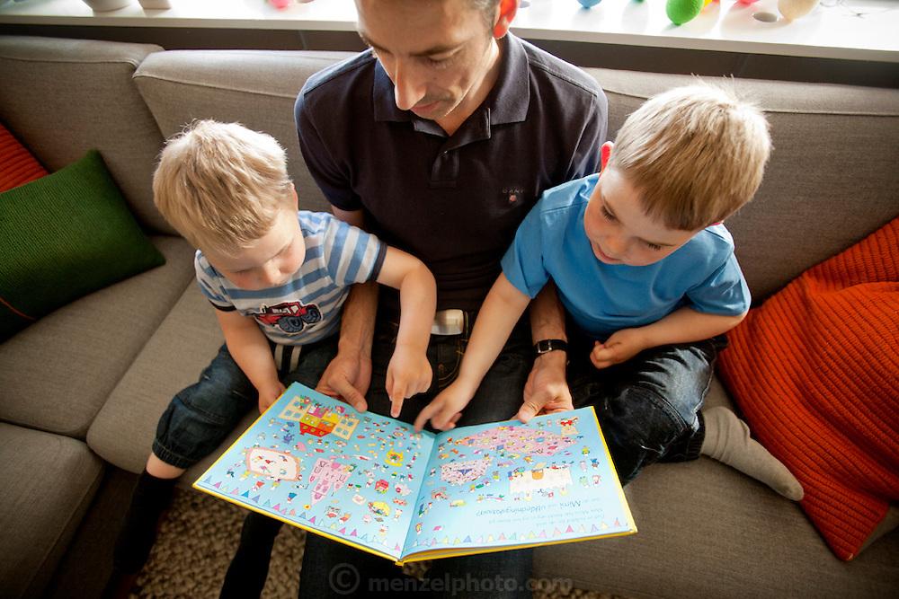 Ottersland Dahl family, of Gjettum, Norway (outside Oslo). Tor Erik Dahn, 39, reading to two of his three sons, Olav, 6 Hakon, 3,
