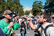 A man from the Los Angeles chapter of Bible Believers (left) and an fan of Pope Francis clash in a war of words following a short parade where Pope Francis was driven on the streets around the Ellipse, south of the White House in Washington, District of Columbia, U.S., on Wednesday, Sept. 23, 2015.  Photographer: Pete Marovich/Bloomberg