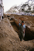 Women digging trenches and carrying dirt in baskets on their heads in Delhi, India;.