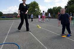 Young boy playing bean bag game in school playground; with teacher watching,