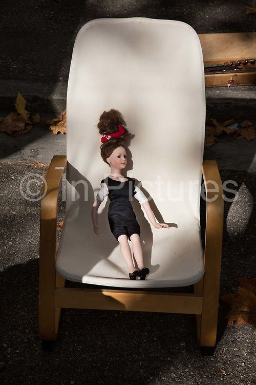 Vintage 50s doll and chair for sale in a brocante on the 17th September 2016, in the village of Lagrasse, France. Brocante, in French, means 'second hand', and these can come in the form of street markets or an indoor market, where vintage goods and antiques are sold by sellers.