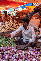 A vendor dealing in eggplant, okra, and potatoes in City Market, Bangalore, India