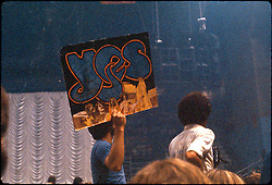 Fans chilling before Yes (Band) performs at the New Haven Coliseum on 9 August 1977. One Fan holds up a hand made poster or banner art of the Yes Logo from an album.