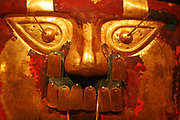 Funerary Mask.  Peru; Sican (Lambayeque) 9th-11th century.  Hammered gold, cinnabar, copper overlays.  The rich tombs of Sican rulers reportedly contained as many as five gold masks along with other precious offerings.