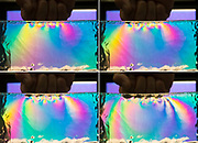 A series of four images showing different amounts of forces. The force generated by a punch is visualized by using polarized light to show the stress generated in ballistic gel.