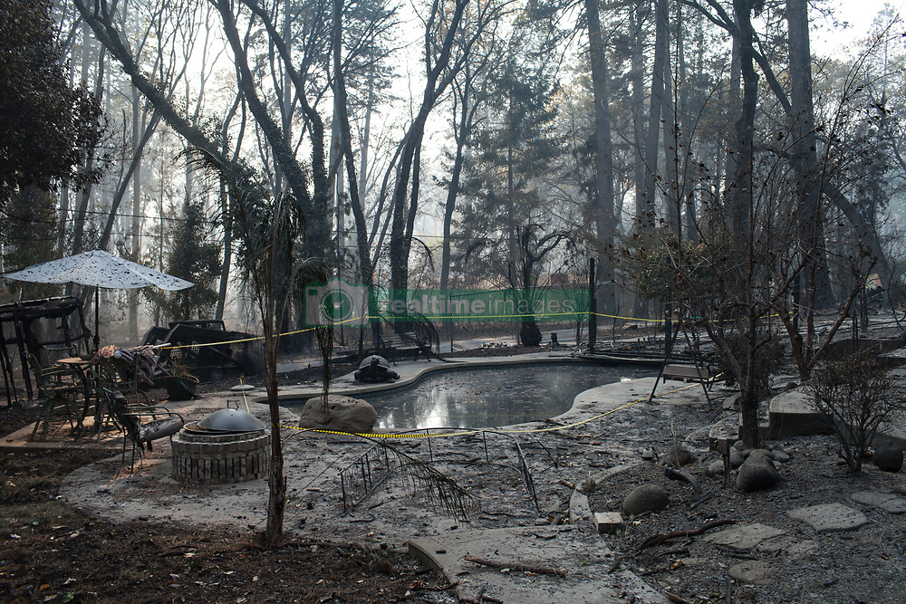 November 17, 2018 - California, USA - Crime tape marking the site of a found body surrounds a pool of a residential home nearby the corner of Cindy and Tabernacle lanes after the Camp Fire ripped through Paradise, California. At least 71 people have been confirmed dead and over 1,000 others remain missing due to the Camp Fire as of Nov. 17 according to the Butte County Sheriff's Department. (Credit Image: © Joel Angel Juarez/ZUMA Wire)