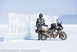 Cold weather adventure motorcyclist and author Alessandro Ciceri, better known as Wizz (@wizz_inwiaggio), after riding 6,200 mile (10,000 km) from his home in Italy in the middle of winter, seen here posing with the ice sculpture sign at the entrance to the Baikal Mile Ice Speed Festival. Maksimiha, Siberia, Russia. Monday, March 2, 2020. Photography ©2020 Michael Lichter.