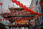 Banner celebrating the state visit to London of Chinese leader Xi Pinjing is attached to the Chinatown gateway covered in scaffolding, flags and lanterns.