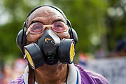 07 AUGUST 2013 - BANGKOK, THAILAND: A Thai anti-government protester wears goggles and a gas mask in case government forces use them against protesters in Bangkok. About 2,500 protestors opposed to an amnesty bill proposed by Thailand's ruling party marched towards the Thai parliament in the morning. The amnesty could allow exiled fugitive former Prime Minister Thaksin Shinawatra to return to Thailand. Thaksin's supporters are in favor of the bill but Thai Yellow Shirts and government opponents are against the bill. Thai police deployed about more than 10,000 riot police and closed roads around the parliament. Although protest leaders called off the protest rather than confront police, a few people were arrested for assaulting police when they tried to break through police lines. Several police officers left the scene under medical care after they collapsed in the heat.    PHOTO BY JACK KURTZ