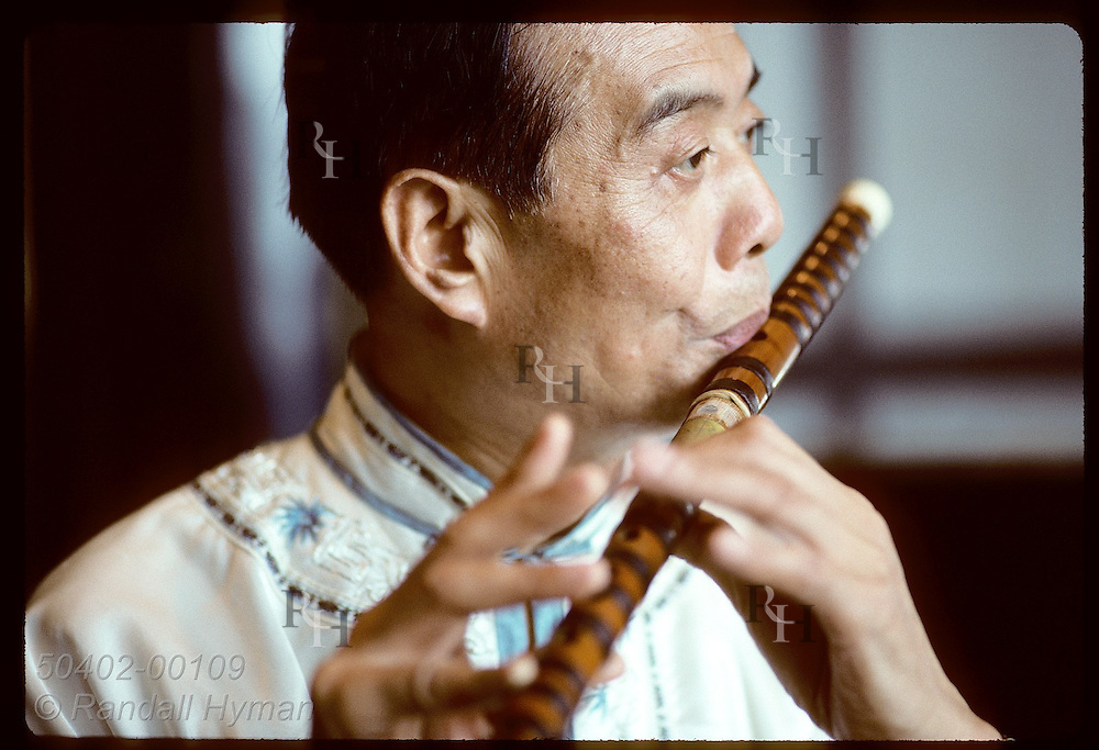 Man plays wooden flute, or ti-tzu, often used in orchestras and played @ weddings, funerals, etc China