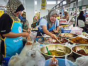 18 JUNE 2015 - PATTANI, PATTANI, THAILAND: Women sell home made curry pastes in the market in Pattani. Many Thai Muslims go shopping early in the day to buy food for Iftar, the meal that breaks the day long Ramadan fast.    PHOTO BY JACK KURTZ