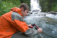 A young man filters water while hiking in Grand Teton National Park, Jackson Hole, Wyoming.