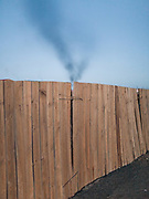 The smoke of a coal factory over a fence in Dalanzadgab.