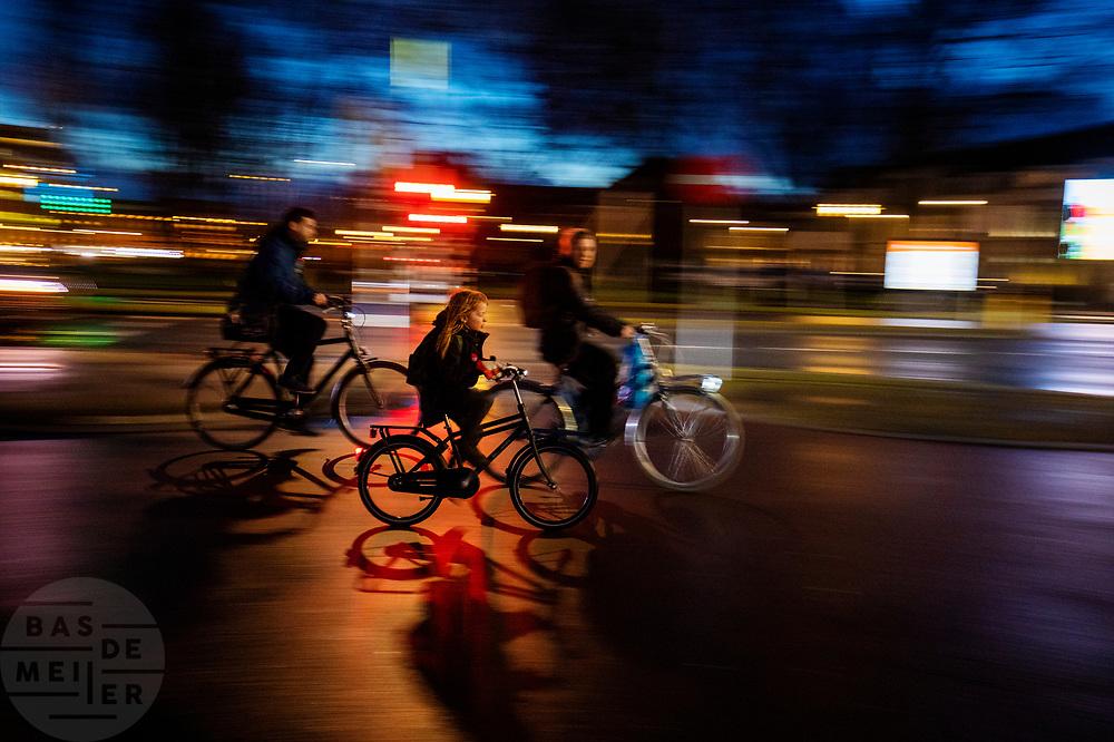 Een vrouw fietst met haar kind 's avonds door Utrecht. De straten zijn nat van de regen.<br /> <br /> A woman cycles with her child in Utrecht on an evening. The streets are wet due to the rain.