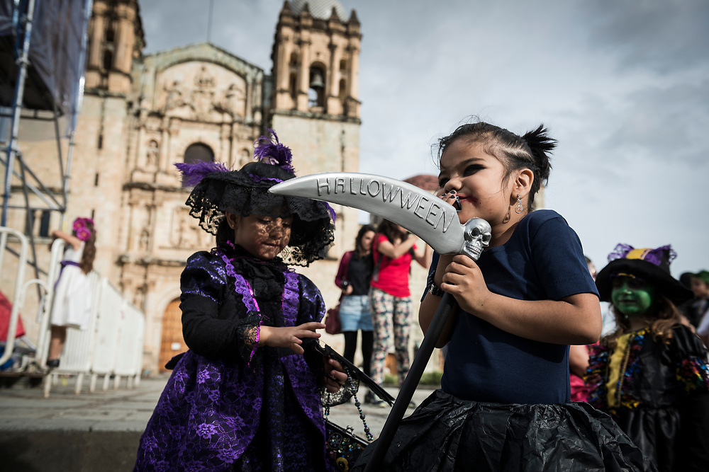 """A girl holds a grim reaper scythe with the word """"Hallowween"""" written on it in Oaxaca, Mexico. The children are in costume as the city celebrates the Day of the Dead (Dia de los Muertos)"""