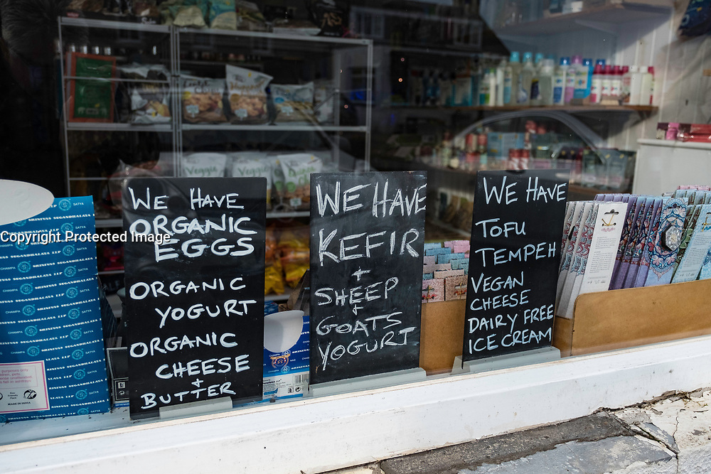 Window display of signs showing organic foods for sale in Deli shop in historic village of Crail in East Neuk of Fife in Scotland , United Kingdom.