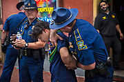 Fake arrest by State Troopers for a selfie on Bourbon Street in the French Quarter during Mardi Gras on 25th February 2020 in New Orleans, Louisiana, United States. Mardi Gras is the biggest celebration the city of New Orleans hosts every year. The magnificent, costumed, beaded and feathered party is laced with tradition and  having a good time. Celebrations are concentrated for about two weeks before and culminate on Fat Tuesday the day before Ash Wednesday and Lent.
