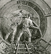 Thames subway between Tower Hill and Vine Street:  Fitting a section of the cast iron lining behind the tunnelling shield. This was the first tunnel to have a cast iron lining. Engraving 1869.