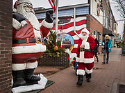 "30 NOVEMBER 2019 - WEST DES MOINES, IOWA: SANTA CLAUS walks past a Santa statue and American flag mural on 5th Street, the main business street in West Des Moines, Saturday. He was handing out gifts to children on Small Business Saturday. ""Small Business Saturday"" was first observed in the United States on November 27, 2010, as a counterpart to Black Friday and Cyber Monday, which are generally considered events at malls, ""big box"" stores and e-commerce retailers. Small Business Saturday encourages holiday shoppers to patronize brick and mortar businesses that are small and local. Small Business Saturday is a registered trademark of American Express.     PHOTO BY JACK KURTZ"