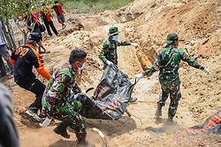 October 4, 2018 - Palu, Central Sulawesi, Indonesia - Officers seen placing the bodies of victims in grave holes  before being mass-buried in Poboya..A deadly earthquake measuring 7.7 magnitude and the tsunami wave caused by it has destroyed the city of Palu and much of the area in Central Sulawesi. According to the officials, death toll from devastating quake and tsunami rises to 1,347, around 800 people in hospitals are seriously injured and some 62,000 people have been displaced in 24 camps around the region. (Credit Image: © Hariandi Hafid/SOPA Images via ZUMA Wire)