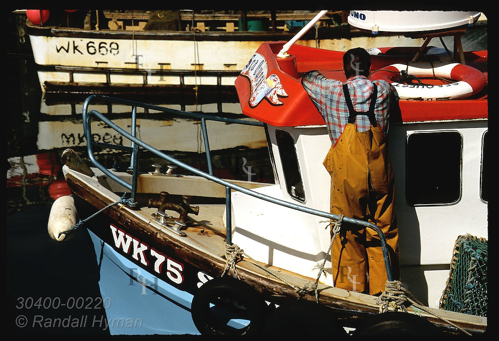 Fisherman stands near bow of boat as it cruises into harbor on a July morning; John O'Groats. Scotland