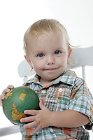 21 July 2008:  One year old toddler Jonah Wells in the studio sitting in a chair holding a small world globe in his hands on white seamless paper silo.