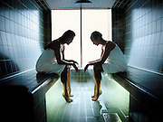 Two women sit in towells inside of a sauna while spending the day at a spa